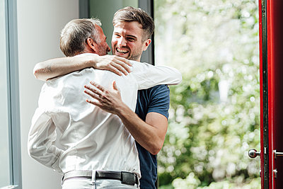 Cheerful son embracing father while standing near door at home - p300m2276990 by Gustafsson