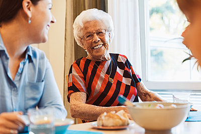 Happy senior woman talking to daughter at dining table - p426m1468262 by Maskot