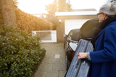 Woman on driveway in front of open car boot holding suitcase - p429m1140094 by Maria Fuchs