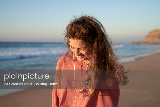 Young woman with earphones on the beach - p1124m1508621 by Willing-Holtz