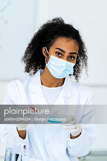 Female researcher in protective face mask working in laboratory - p300m2266224 by Giorgio Fochesato