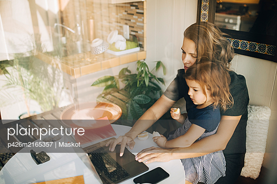 Mother using laptop while daughter sitting on lap seen through glass window - p426m2165357 by Maskot