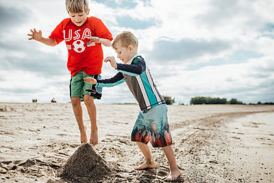 Happy brothers playing with sand at beach against cloudy sky - p1166m2001063 by Cavan Images