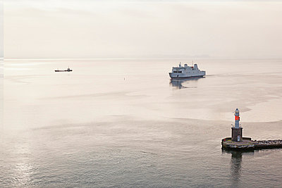 View of arriving ferryboat at harbour entrance with lighthouse at dusk - p30020857f by Mel Stuart
