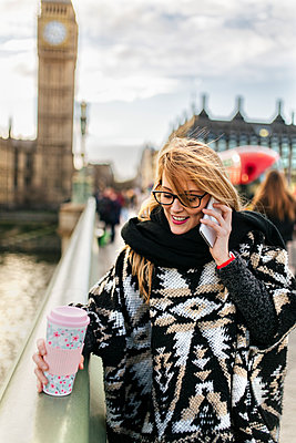 UK, London, young woman talking on phone on Westminster Bridge - p300m1120676f by Marco Govel