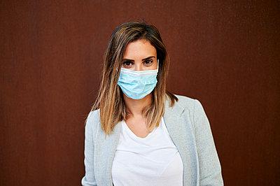 Businesswoman wearing face mask against brown wall - p300m2206794 by Kiko Jimenez