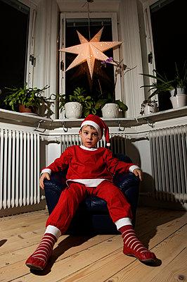 Boy wearing santa hat sitting on armchair - p5756145f by Schlyter, Fredrik