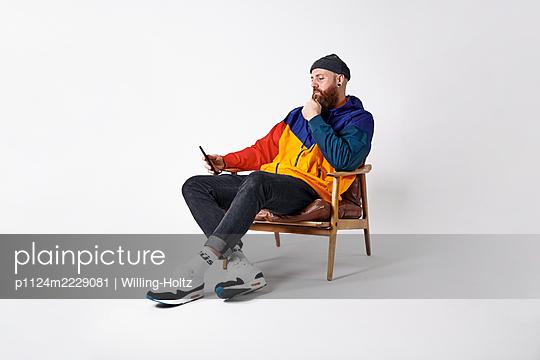 Mann in bunter Sportkleidung mit Smartphone - p1124m2229081 von Willing-Holtz