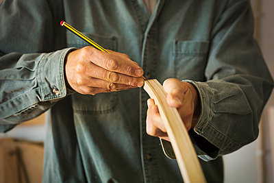 A craftsman using a pencil and marking a piece of curved wood.  - p1100m1522487 by Mint Images