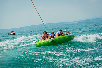 Young people doing water sports on hover tube - p1437m2013338 by Achim Bunz