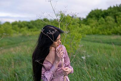 Frau in lila Kleid auf einer Wiese - p1646m2257571 von Slava Chistyakov