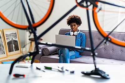Young woman using laptop on sofa seen through bicycle at home - p300m2274811 by Giorgio Fochesato