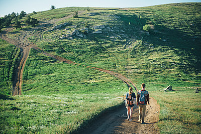 Caucasian couple walking on path toward hill - p555m1231813 by Ivan Evgenyev