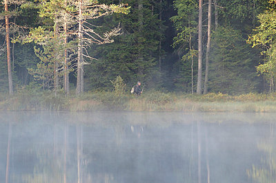 Fisherman on lakeshore with fog - p5756931 by Stefan Ortenblad