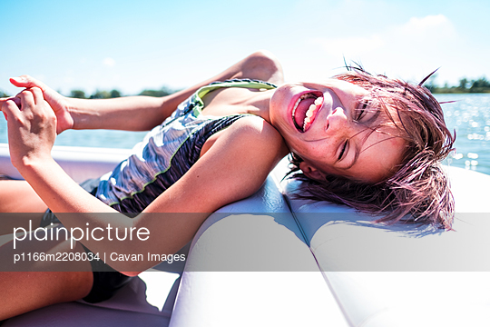 Laughing girl on a boat in hawaii - p1166m2208034 by Cavan Images
