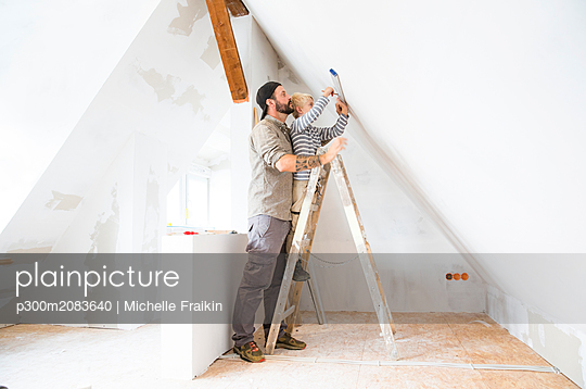 Father and son working on loft conversion using water level - p300m2083640 by Michelle Fraikin