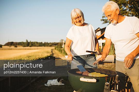 Couple preparing food on grill in garden - p312m2237430 by Amanda Falkman