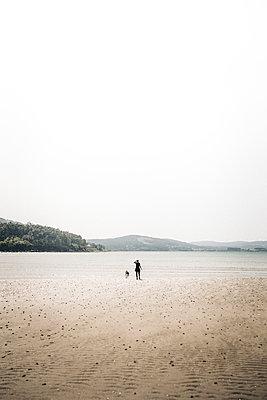 Junge Frau mit Hund am Strand in weiter Ferne - p1497m2090417 von Sascha Jacoby