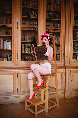 Women reading a book in vintage lingerie  - p1521m2215051 by Charlotte Zobel