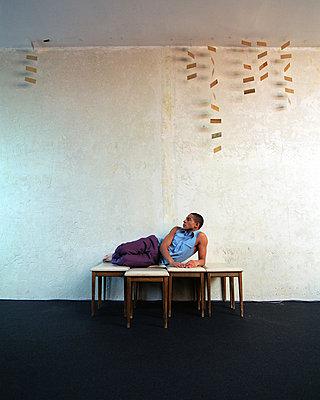 Junger Mann liegt auf Hockern - p2682101 von Rui Camilo