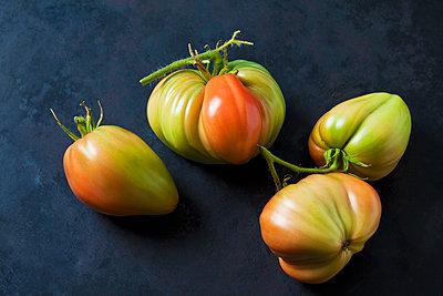 Four Oxheart tomatoes on dark ground - p300m2079279 by Dieter Heinemann