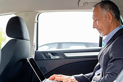 Businessman working on laptop while sitting in car - p300m2287336 by Emma Innocenti