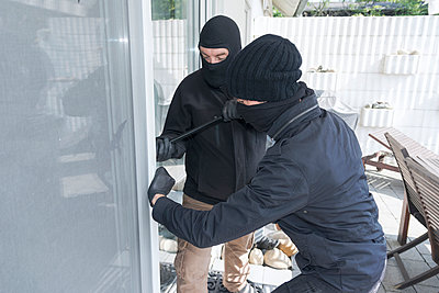 Two burglars opening terrace door of an one-family house with hammer and crowbar at daytime - p300m965538f by noonland