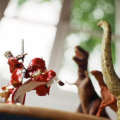 Toy knight fighting against toy dinosaurs. - p62317540f by Christian Zachariasen