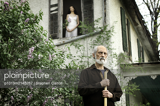 Man in front of a house, woman on window - p1019m2148287 by Stephen Carroll