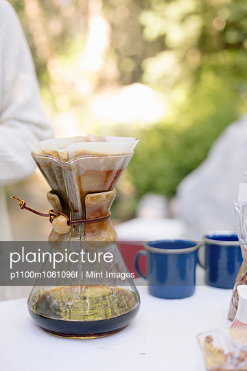 Close up of a glass coffee maker on a table in a garden.