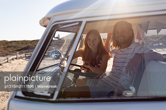 Young couple sitting together in front seat of camper van at beach - p1315m2117896 by Wavebreak