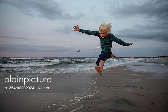 Jumping boy at the beach - p1354m2292924 by Kaiser