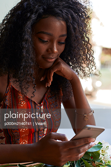 Portrait of young African woman in a cafe, checking her smartphone - p300m2140741 by Veam