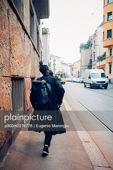 Young man with backpack walking on road - p300m2276778 by Eugenio Marongiu