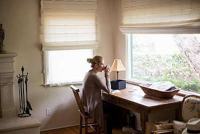 Blond woman sitting at a desk by a window, drinking a cup of tea. - p1100m1080237 by Mint Images