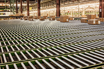 Interior view of a gravity feed conveyor system in a large distribution warehouse with products stored  in cardboard boxes - p1100m1575474 by Mint Images