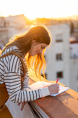Smiling young woman taking notes on roof terrace at sunset - p300m2083053 by VITTA GALLERY