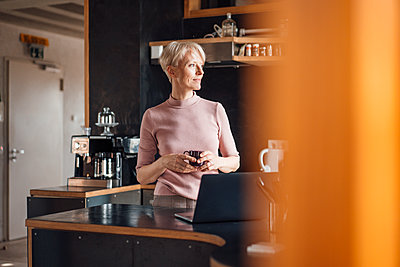 Smiling businesswoman looking away while holding coffee cup in kitchen at home office - p300m2266984 by Robijn Page