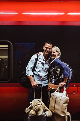 Portrait of happy couple with luggage standing against train at railroad station - p426m2145999 by Maskot
