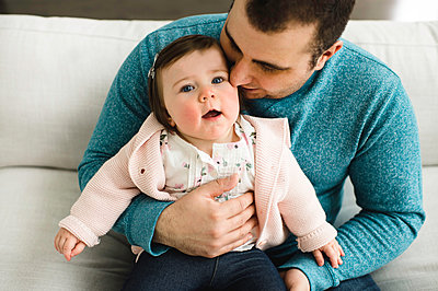 Baby girl looking up while being snuggled by her father - p429m1407711 by Erin Lester