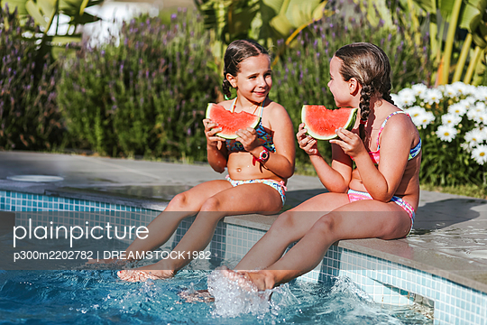 Happy twin girls sitting with watermelon slice at poolside on sunny day - p300m2202782 by DREAMSTOCK1982