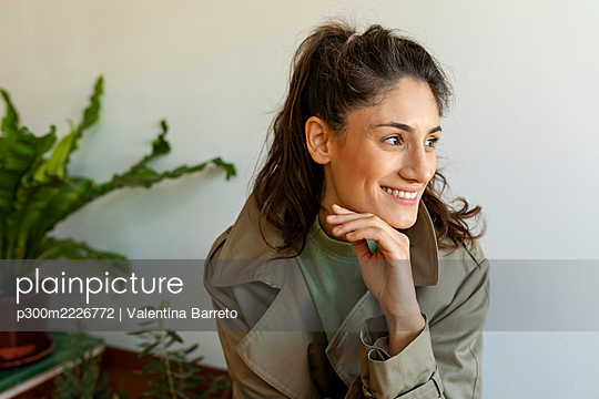 Smiling woman with hand on chin looking away sitting against wall - p300m2226772 by Valentina Barreto