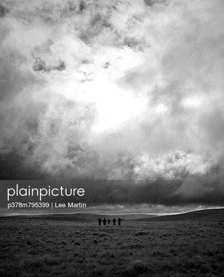 Walkers crossing cloudy moorland - p378m795399 by Lee Martin