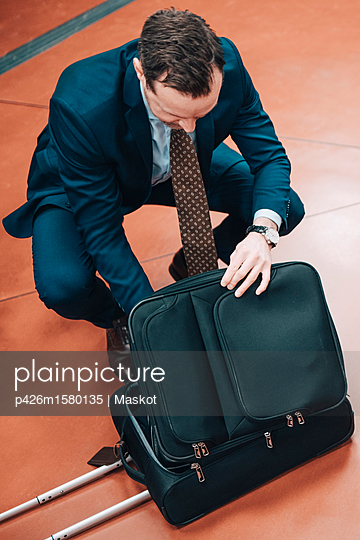 High angle view of businessman with suitcase at subway station - p426m1580135 by Maskot