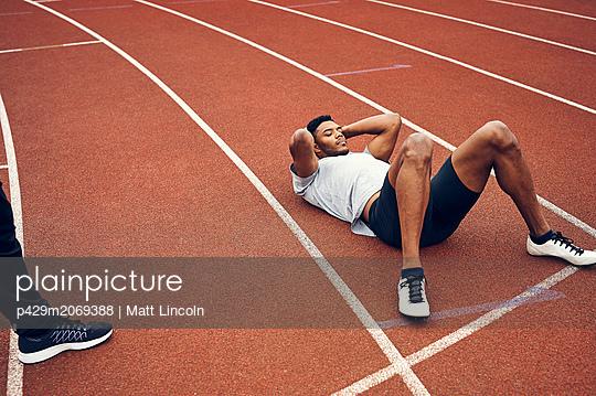 Runners resting on running track - p429m2069388 by Matt Lincoln