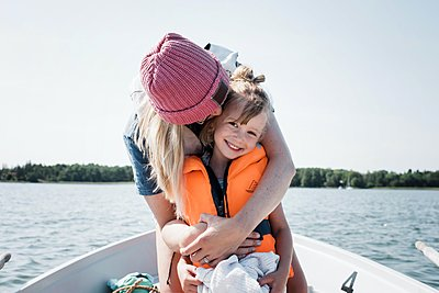 mother hugging happy daughter whilst on a boat in summer in Sweden - p1166m2205677 by Cavan Images