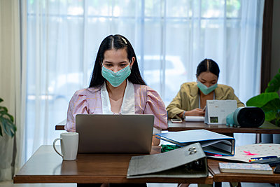 Asian business people wear protective face mask due covid workin - p1166m2246644 by Cavan Images