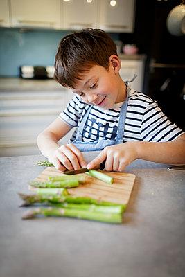 7 year old boy cuts green asparagus and potatoes in modern kitchen, lower Austria - p300m2180224 von Epiximages