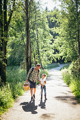 Daughter talking to father holding picnic basket on road in forest - p426m2213187 by Maskot