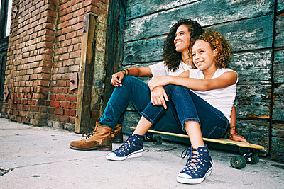 Mixed race mother and daughter sitting on skateboard - p555m1410418 by Peathegee Inc